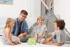 Męski opiekunka do dziecka bawić się z dziećmi Zdjęcia Stock