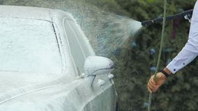 Męski opryskiwanie samochód z mydlastą pianą, kierowca bierze opiekę pojazd, carwash zdjęcie wideo