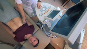Męski pacjent dostaje jego podbrzusze skanuje ultradźwięk maszyną zbiory
