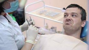 Męski pacjent kłama na stomatologicznym krześle w klinice, opowiada lekarka, ono uśmiecha się i przygotowywa dla procedur, zbiory
