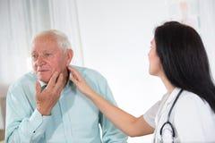 Męski pacjent mówi lekarkę o jego zdrowie skargach Zdjęcie Stock