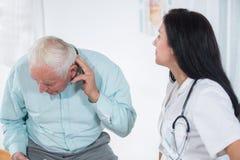 Męski pacjent mówi lekarkę o jego zdrowie skargach Zdjęcia Royalty Free