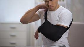 Męski pacjent przystosowywa ręka temblaka w właściwej pozycji, rehabilitacja po urazu zbiory