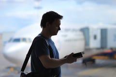 Męski pasażer przy lotniskiem z samolotem na tle Zdjęcia Royalty Free