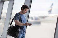 Męski pasażer przy lotniskiem z samolotem na tle Zdjęcie Stock
