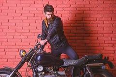 Męski pasyjny pojęcie Mężczyzna z brodą, rowerzysta w skórzanej kurtki blisko silnika rowerze w garażu, ściana z cegieł tło fotografia royalty free
