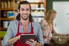 Męski personel trzyma cyfrową pastylkę i sprawdza sklepów spożywczych produkty na półce Obrazy Royalty Free