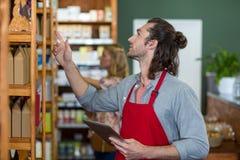 Męski personel trzyma cyfrową pastylkę i sprawdza sklepów spożywczych produkty na półce Obraz Royalty Free