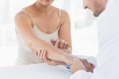 Męski physiotherapist egzamininuje rękę kobieta Obraz Stock