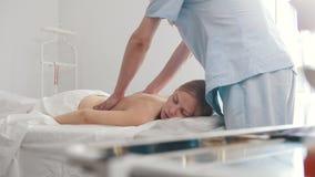 Męski physiotherapist masowania kobiety ` s plecy w medycznym biurze zdjęcie wideo