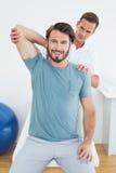 Męski physiotherapist rozciąga ono uśmiecha się obsługuje rękę Obraz Stock