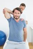 Męski physiotherapist rozciąga uśmiechnięty młodego obsługuje rękę Obrazy Stock