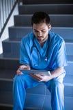 Męski pielęgniarki obsiadanie na schody i używać cyfrową pastylkę Zdjęcie Royalty Free