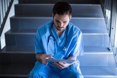 Męski pielęgniarki obsiadanie na schody i używać cyfrową pastylkę Obraz Royalty Free