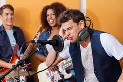 Męski piosenkarz Jest ubranym hełmofony Podczas gdy Wykonujący Obrazy Stock