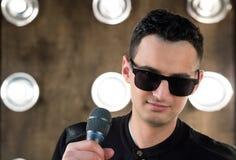 Męski piosenkarz w okularach przeciwsłonecznych z mikrofonu spełnianiem w projecto Zdjęcia Royalty Free