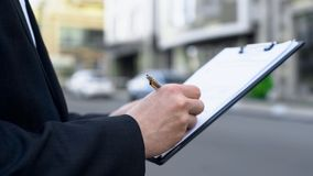 Męski pośrednik handlu nieruchomościami pisze w górę listy potencjalne nabywcy, hipoteczna decyzji kolejka fotografia stock