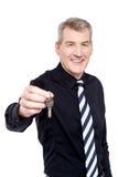 Męski pośrednik handlu nieruchomościami pokazuje klucze kamera Obrazy Royalty Free