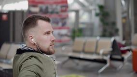 Męski podróżnik czeka samolot, pociąg w sali lub słuchającą muzykę słuchawki zbiory wideo