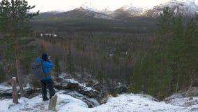 Męski podróżnik jest fotografem stoi na wysokim punkcie w górach i podziwia pięknego widok, Patrzeje zbiory