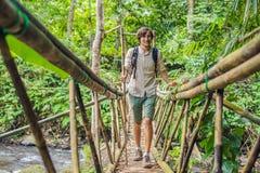 Męski podróżnik na zawieszenie moście w Bali zdjęcie stock