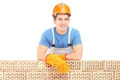 Męski pracownik budowlany odpoczywa na ściana z cegieł Zdjęcie Royalty Free