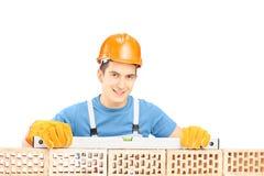 Męski pracownik budowlany trzyma narzędzie na ściana z cegieł Zdjęcia Royalty Free