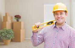 Męski pracownik budowlany Trzyma poziom W pokoju Z chodzeń pudełkami Zdjęcia Royalty Free