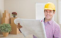 Męski pracownik budowlany Trzyma rolkę błękit W pokoju Z pudełkami Fotografia Stock