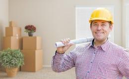 Męski pracownik budowlany Trzyma rolkę błękit W pokoju Z pudełkami Zdjęcia Stock