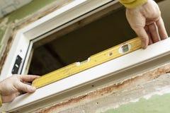 Męski pracownik instaluje UPVS okno używać poziom zdjęcia royalty free