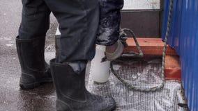 Męski pracownik jest ubranym czarnych gumowych buty wiąże w górę białej butelki z gęstą arkaną zbiory wideo