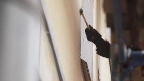 Męski pracownik jest ubranym pomarańcze mundur uderza beż ścianę z małym młotem zbiory wideo