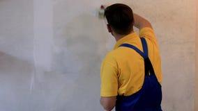 Męski pracownik maluje ścianę z białym kolorem w błękitnych coveralls zbiory wideo