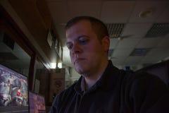 Męski pracownik ochrony na miejsc pracy spojrzeniach przy monitor depresji ligth obrazy stock