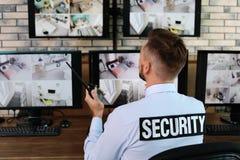 Męski pracownik ochrony z przenośnym nadajnikiem monitoruje nowożytne CCTV kamery obrazy royalty free