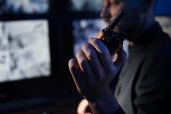 Męski pracownik ochrony z przenośnym nadajnikiem monitoruje nowożytne CCTV kamery indoors zdjęcia stock