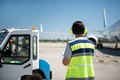 Męski pracownik patrzeje samolot w hełmofonach podczas gdy partnera obsiadanie w pojazdzie obrazy royalty free