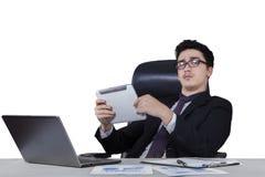 Męski pracownik trzyma pastylkę przy biurkiem Obrazy Stock