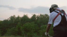 Męski pracownik w kombinezonach i ochronnej maski tnącej trawie zdjęcie wideo