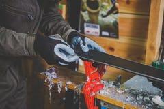 Męski pracownik w narciarskim usługowym warsztacie naprawia ślizgową powierzchnię narty Zakończenie ręka z plastikowym scrapper d obrazy stock