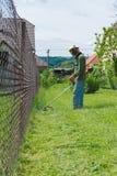 Męski pracownik z władzy narzędzia sznurka gazonu drobiażdżarką mo Fotografia Stock