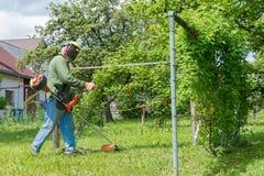 Męski pracownik z władzy narzędzia sznurka gazonu drobiażdżarką mo Zdjęcia Stock