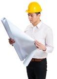 Męski pracownika budowlanego czytanie na błękitnym druku Fotografia Royalty Free