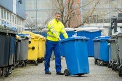 Męski pracownika odprowadzenie Z kosz na śmiecie Na ulicie Zdjęcia Stock