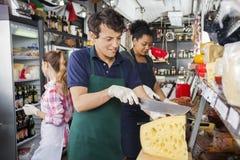 Męski pracownika przecinania ser Z nożem W sklepie Obrazy Royalty Free