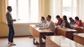 Męski profesor w przypadkowych ubraniach opowiada grupa ucznie siedzi przy stołami w sala lekcyjnej i robi notatkom ampuła zbiory