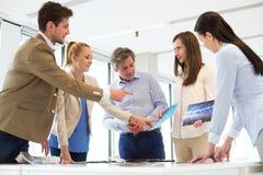 Męski projekta profesjonalista z drużyną dyskutuje przy stołem w nowym biurze Fotografia Stock