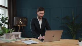 Męski projektant w biurowym działaniu na laptopie z modela domem zbiory wideo