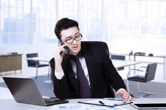 Męski przedsiębiorca wyjaśnia raport na telefonie komórkowym Obraz Royalty Free